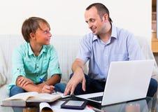 Взрослые человек и мальчик с компьтер-книжкой внутри помещения Стоковое Изображение