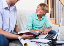 Взрослые человек и мальчик с компьтер-книжкой внутри помещения Стоковые Изображения