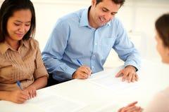 Взрослые этнические пары подписывая контракт Стоковое Изображение