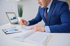Взрослый бизнесмен работая в офисе Стоковое Фото