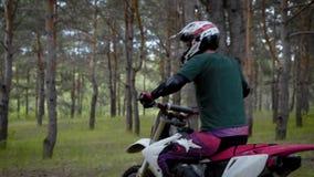 Взрослый водитель мотоцикла управляет через лес более часто в дневном времени, человек нес защитный шлем над его акции видеоматериалы