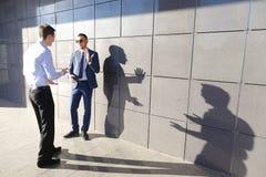 Взрослый 2 детенышей укомплектовывает личным составом предпринимателей обсуждая важные вопросы, Стоковая Фотография