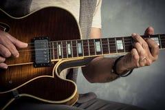 Взрослый кавказский портрет гитариста играя электрическую гитару на предпосылке grunge Закройте вверх по детали аппаратуры нот Стоковые Фотографии RF