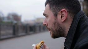 Взрослый один человек ест горячую сосиску в городе на стенде акции видеоматериалы