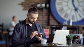 Взрослый парень выпивает кофе в современном кафе, человек при волосы tucked в его кабель просматривает самые последние новости на сток-видео