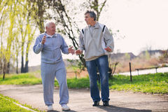 Взрослый сын идя с его старшим отцом стоковая фотография rf