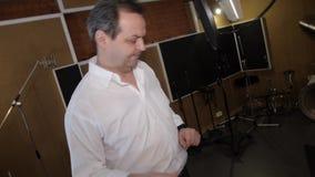 Взрослый человек в белой рубашке поет в студии перед микрофоном щелкая перста видеоматериал