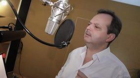 Взрослый человек в белой рубашке поет в студии перед микрофоном Ядровая запись видеоматериал