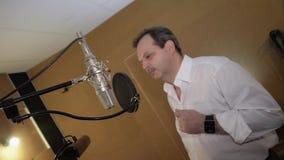 Взрослый человек в белой рубашке поет в студии перед микрофоном Ядровая запись сток-видео