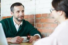 Взрослый человек и женщина беседуя в кафе над кофе Стоковая Фотография RF
