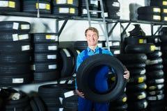 Взрослый человек механика стоя с новыми автошинами автомобиля Стоковое Фото