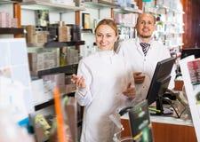 2 взрослых аптекаря стоя рядом с полками Стоковое Изображение