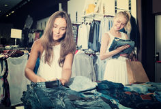 2 взрослых девушки выбирая брюки джинсовой ткани Стоковые Фото