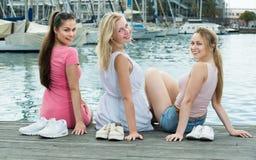 3 взрослых девушки сидя на пристани в городке Стоковое фото RF