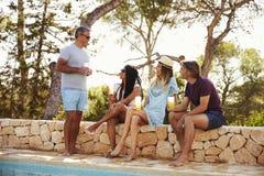 2 взрослых пары общаясь outdoors бассейном Стоковое Изображение