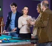 2 взрослых пары различных поколений выпивают вино внутри Стоковые Изображения RF
