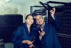 2 взрослых работника винодельни держа бутылку вина Стоковые Изображения