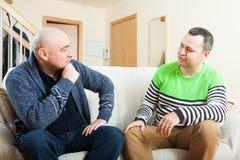 2 взрослых друз говоря дома Стоковые Изображения
