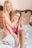 2 взрослых сестры в пижамах лежа на белой кровати Стоковые Изображения
