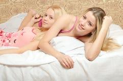 2 взрослых сестры в пижамах лежа на белой кровати Стоковое фото RF