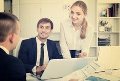 3 взрослых сотрудника имея переговор стоковое фото