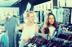 2 взрослых усмехаясь девушки выбирая платье совместно Стоковая Фотография