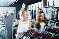 2 взрослых усмехаясь девушки выбирая платье совместно Стоковая Фотография RF