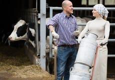 2 взрослых фермера держа вагонетку с молоком Стоковые Изображения