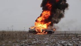 Взрыв автомобиля, взгляд со стороны, ожога автомобиля в сером поле акции видеоматериалы