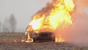 Взрыв автомобиля, вид спереди, ожога автомобиля в сером поле видеоматериал
