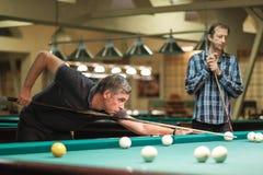 Взятия игрока направляют на шарик в биллиардах Стоковая Фотография