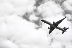 Взлет самолета от взлётно-посадочная дорожка на облачном небе черная белизна Стоковое Фото
