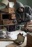 Взломщик крадя детали от спальни во время пролома дома внутри Стоковое Изображение RF