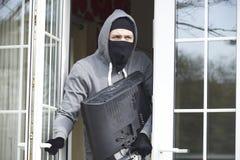 Взломщик ломая в дом и крадя телевидение стоковое фото