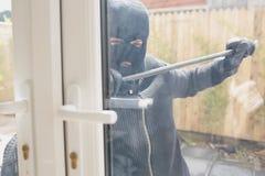 Взломщик раскрывая дверь с ломом Стоковые Фото