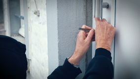 Взломщик с дверью пролома замк-рудоразборки для того чтобы войти дом видеоматериал