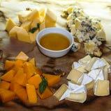 4 вида сыра с медом и хлебом стоковое фото