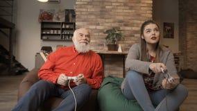 Видеоигра игры старшего человека с маленькой девочкой сток-видео