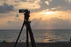 Видеокамера снимая пляж на заходе солнца на море Стоковые Фото