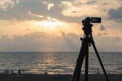 Видеокамера цифров снимая пляж на заходе солнца на море twilight ландшафт неба и облака Стоковая Фотография RF
