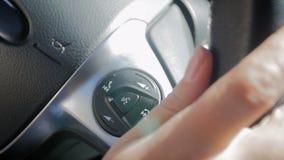 Видео замедленного движения крупного плана водителя автомобиля регулируя управление круиза и radion автомобиля используя ручки на видеоматериал