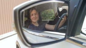 Видео замедленного движения крупного плана красивой усмехаясь женщины регулируя зеркала автомобиля перед ездой сток-видео