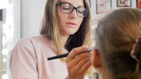 Видео замедленного движения крупного плана профессионального визажиста прикладывая косметики и подготавливая молодую женскую моде видеоматериал