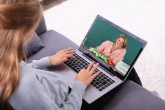 Видео конференц-связь девушки с учителем на ноутбуке стоковое изображение