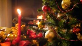Видео крупного плана 4k накалять освещает на украшенной рождественской елке, свече и горящем камине Совершенная предпосылка для видеоматериал