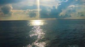 Видео- лучи солнца светя на облачном небе поверхности океана мерцающем светлом красивом видеоматериал