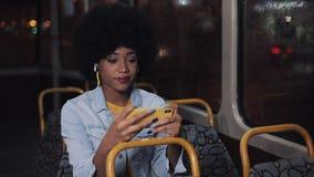 Видео молодой Афро-американской женщины наблюдая на катании смартфона в общественном транспорте Nighttime : e сток-видео