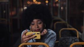 Видео молодой Афро-американской женщины наблюдая на катании смартфона в общественном транспорте Nighttime : e видеоматериал
