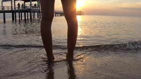 Видео, ноги женщины на море волн песка пляжа на восходе солнца сток-видео