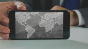 Видео произведенное цифров бизнесмена держа мобильный телефон с картой мира